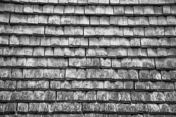 Old traditional wooden tiled roof. Aged photo. Black and white.