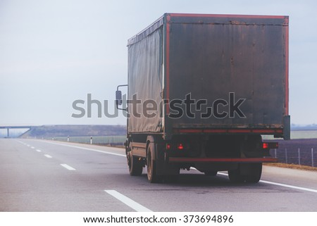 Old trailer truck in motion on Eastern Europe freeway, cargo transportation. #373694896