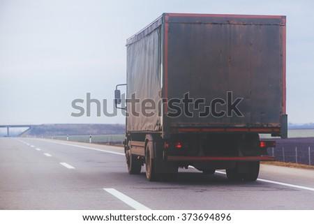 Old trailer truck in motion on Eastern Europe freeway, cargo transportation. #373694896
