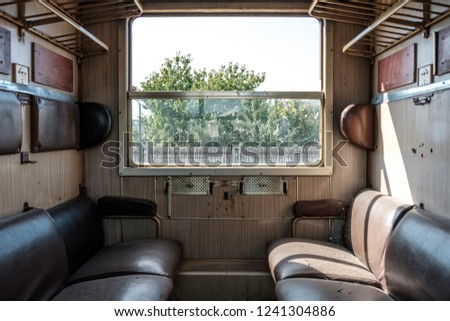 Old train cabin of second class in abandoned train with leather seats facing each other and sun shining through the open window of passenger compartment