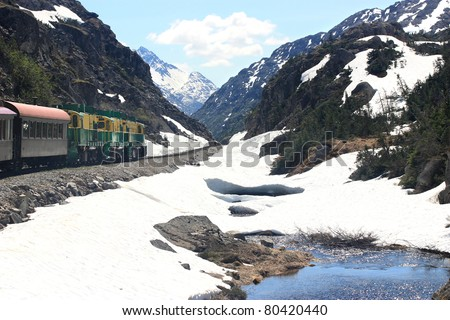 Old train traveling through snowy mountain