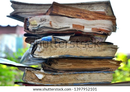 Old treatise books that were flooded,dirty, dried were arranged in high heaps.