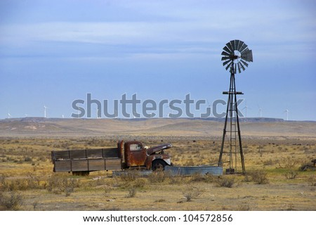 Old truck in an empty field next to an old-style windmill, with new turbine windmills in the distance on the horizon
