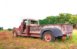 Old truck is being reclaimed by nature in a meadow along with an old tractor wheel in Thailand.