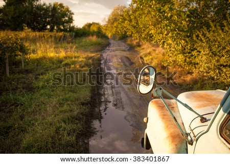 Old truck traveling on the road among fields. After the rain. Puddles and mud on the road. Country road among the vineyards