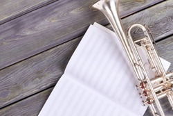 Old trumpet on musical notes sheet. Musical notes and vintage trumpet on wooden background with copy space.