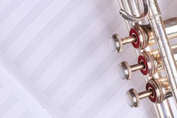 Old trumpet on musical notes sheet. Vintage musical instrument and copy space. Blank notebook for musical notes and wind instrument.