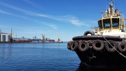 Old tugboat mooring in maritime port with calm blue water. Marine port industrial seascape. Used black tires at shipboard of tug