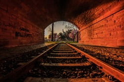 Old tunnel with railroad track in the evening at sunset. Frankfurt skyline at the tunnel exit. Park with trees and meadow in spring with flowers