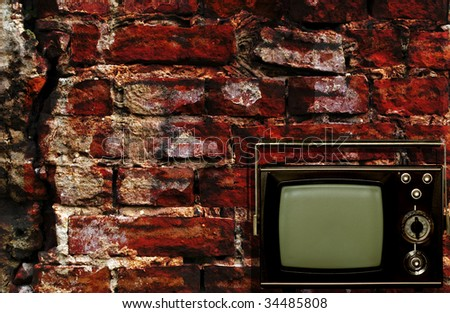 Old tv box with grunge antique wall background