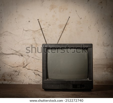 Old tv on wood with grunge background