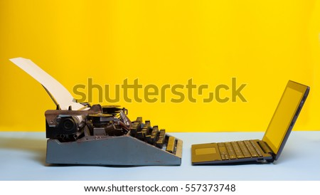 Old typewriter and laptop on table on yellow background. Concept of technology progress. Old vs new; Modern  laptop and an old vintage black typewriter. Space for your text. #557373748