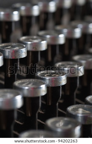 Old typewriter keyboard with silver and black round keys background.