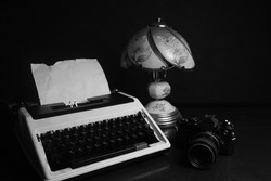 Old Typewriter with a vintage paper beside lamp and analog camera, captured in black and white filters.