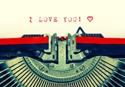 Old typewriter with sample text I LOVE YOU! Red words with heart on white paper. Retro style toned picture
