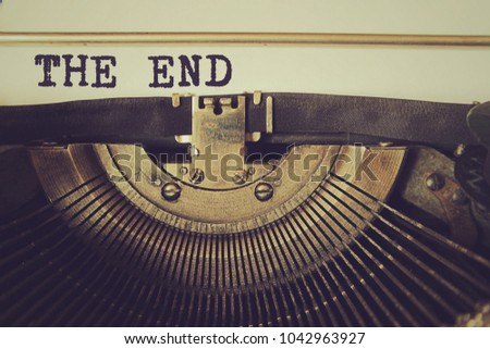 Old typewriter writes text 'The End' on a piece of paper. Vintage toned photo. Stockfoto ©