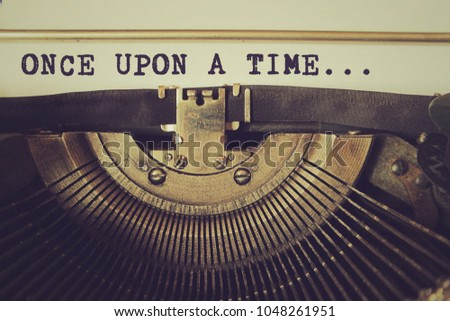 Old typewriter writes word 'once upon a time' on a piece of paper. Vintage toned photo. Stockfoto ©