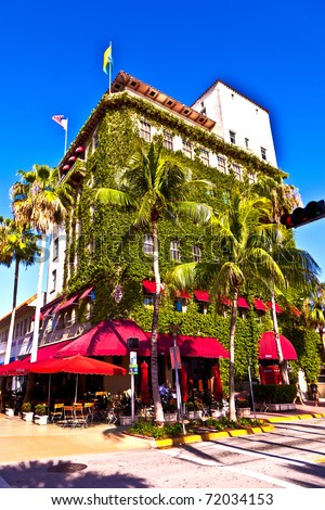 old typical building in art deco style in South Miami with climbing plants and a cafe