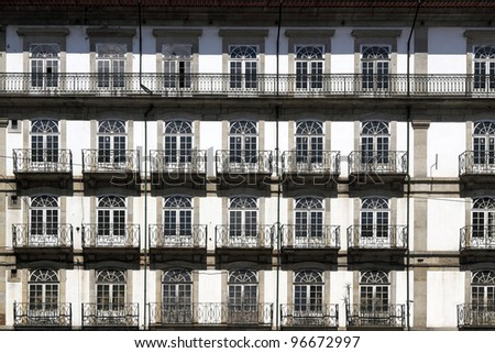 Old typical granite construction of  Porto with wooden windows and doors and iron balconies, geometric, originating interesting pattern