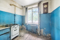 Old ugly abandoned empty kitchen in a residential building. The interior of the collapsing room of the kitchen in the house