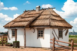 Old Ukrainian hut coated with clay, national traditional house of Slavs with a roof made of reeds or straw