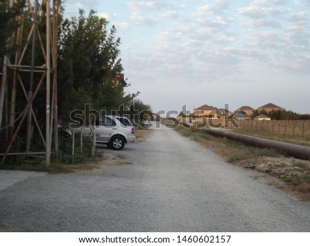 Old unpaved village road, there is a white car on left side and there is an oil pipe on right side. Baku - Azerbaijan: July 2019 #1460602157
