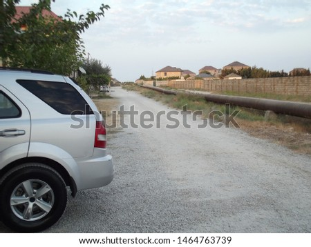 Old unpaved village road, there is a white car on left side and there is an oil pipe on right side. Baku - Azerbaijan: July 2019 #1464763739
