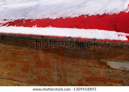 Old upturned snow covered wooden boat in winter with peeling paint