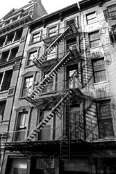 old urban building with fire escape in new york , monotone