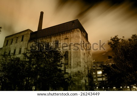 Old urban industrial building with dramatic night sky and clouds