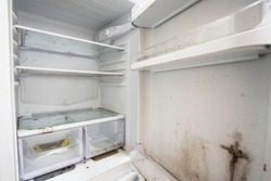 Old used dirty refrigerator with mold,aged junk in the kitchen