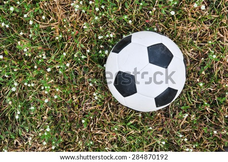 Old used football or old soccer ball on the ground