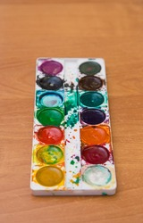 Old used set of multicolored watercolor paints for painting on the table. Top view of half-empty jars of watercolors. Flat layout on the table.
