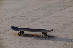 Old used Skateboard is standing on asphalt with tire tracks, Sofia, Bulgaria, Europe