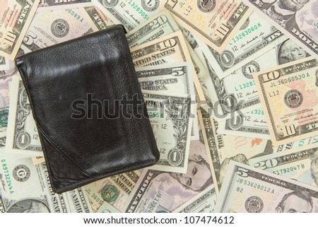 Old used wallet with dollars isolated on dollar bills