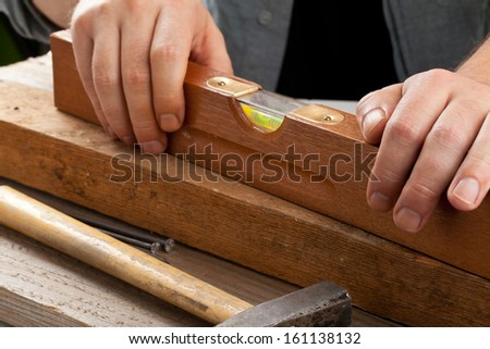 Old used water-level on wooden plank - do-it-yourself or artisan concept - stock photo