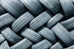 Old used weared car and truck wheels tyres pile stacked in rows stored for recycling. Heap of many rubber tires wall background. Idustrial pollution of environment