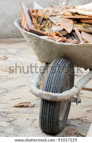 old used wheelbarrow details with construction waste, broken tiles pieces