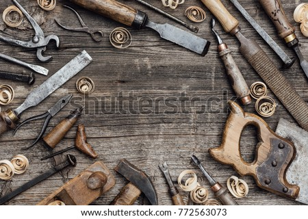 Old used woodworking tools on a vintage workbench composing a frame: carpentry, craftsmanship and handwork concept