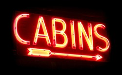 Old vacation camp cabins rental place vintage neon sign with direction arrow glowing in the dark with diffused red glow