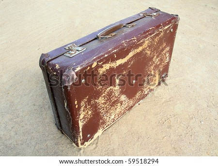old valise on yellow sand