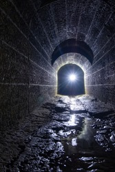 Old vaulted flooded round underground drainage sewer tunnel with dirty sewage water