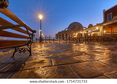 old venetian Harbor Ghania Creta Greece towards to the lighthouse in dawn ligth with reflections in puddles , a bench old street lights and restaurants and the Mosque Küçük Hasan in the foreground Stok fotoğraf ©