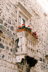 Old Venetian small balcony with white stone columns with beautiful patterns, rectangular clay pots and red blooming flowers, against stone wall of a house in the city of Kotor, Montenegro