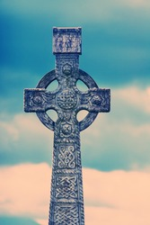 Old Victorian gravestone cross at Cashel cemetery in Ireland processed with colour process filter.