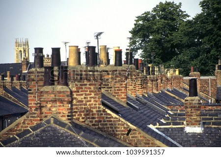 Old Victorian terraced house chimney stacks and chimney pots in lines in the City of York, UK