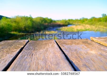 Old village wooden bridge across the river #1082768567