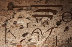 Old vintace tools hanging on Antique wall.  Pitchfork, shovel, iron, saw, old lock and keys, hammer, scythe, knives, pickaxe, scythe. Rusty iron metal tools.