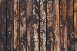 Old vintage aged grunge brown and gray wooden floor planks texture background with dark black stains and contrast light scratches