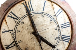 Old vintage and retro analogue clock displaying five o' clock. Worn-out and grunge style with wooden background.